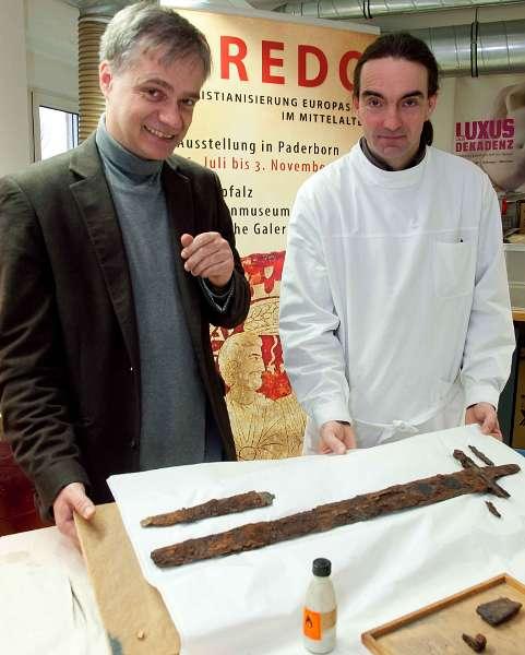 Dr. Martin Kroker und Andreas Weisgerber begutachten das Schwert des Fürsten. (Foto:LWL/Brentführer)