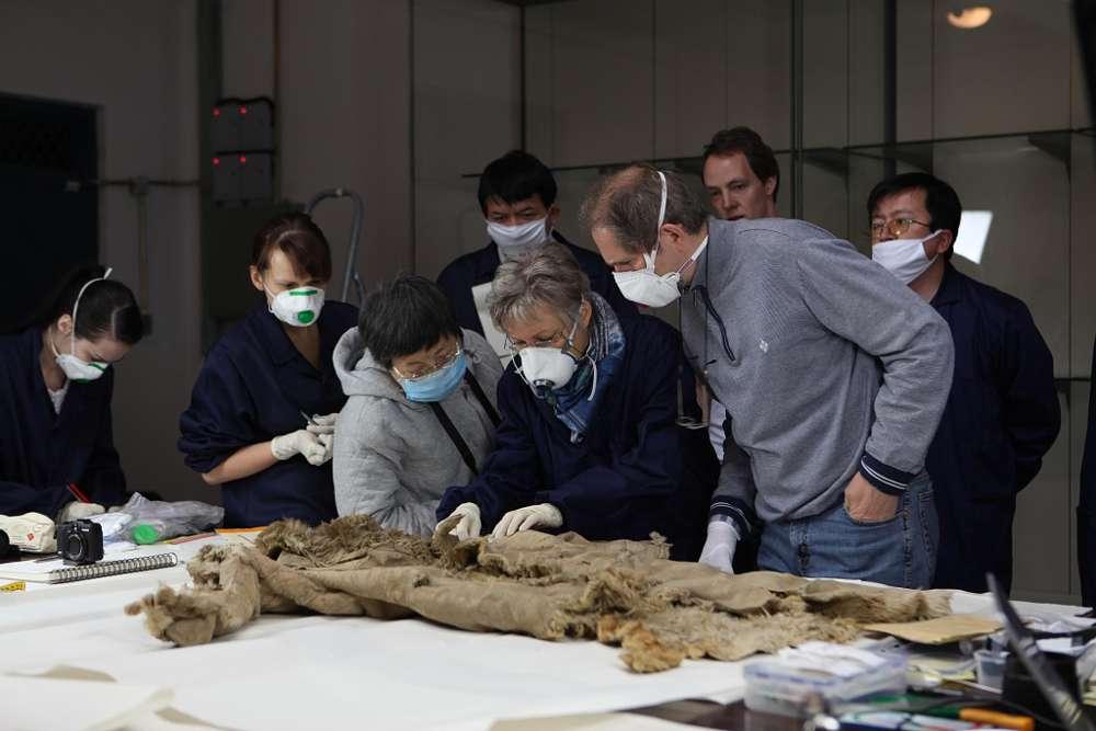 Deutsche und chinesische Wissenschaftler untersuchen einen Fellmantel aus Hami, Xinjiang (Foto: DAI)