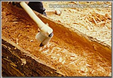 Dechselarbeiten an einem Einbaum mit Hilfe eines Gerade geschäfteten Steinbeiles
