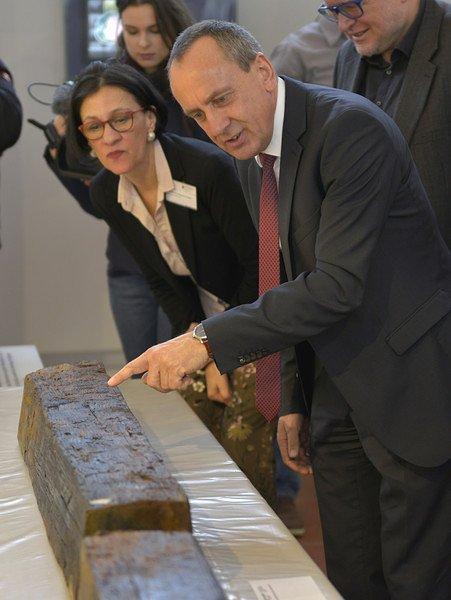 Kulturminister Wolf präsentiert die gefundenen Hölzer